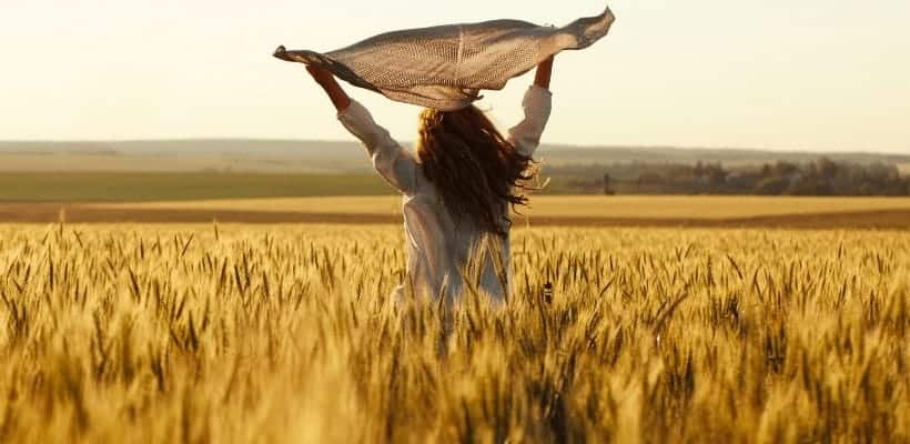 an image of a woman jumping in the air with her arms spread wide 27 Bible Verses About Overcoming Guilt as a Christian featured