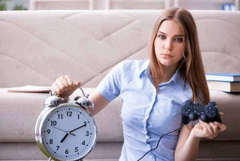 an image of a woman sitting in the floor in front of a couch holding a huge alarm clock with text reading Binding the Spirit Of Distraction to Spiritual Attention