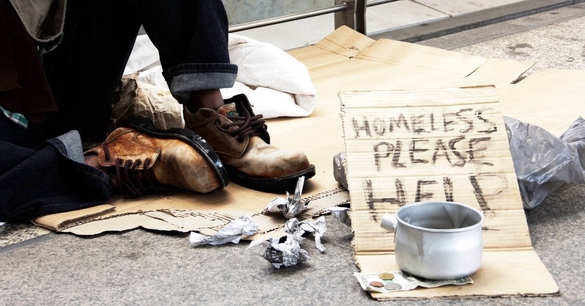 a homeless laying on a cardboard box with a sign that reads homeless and hungry please help