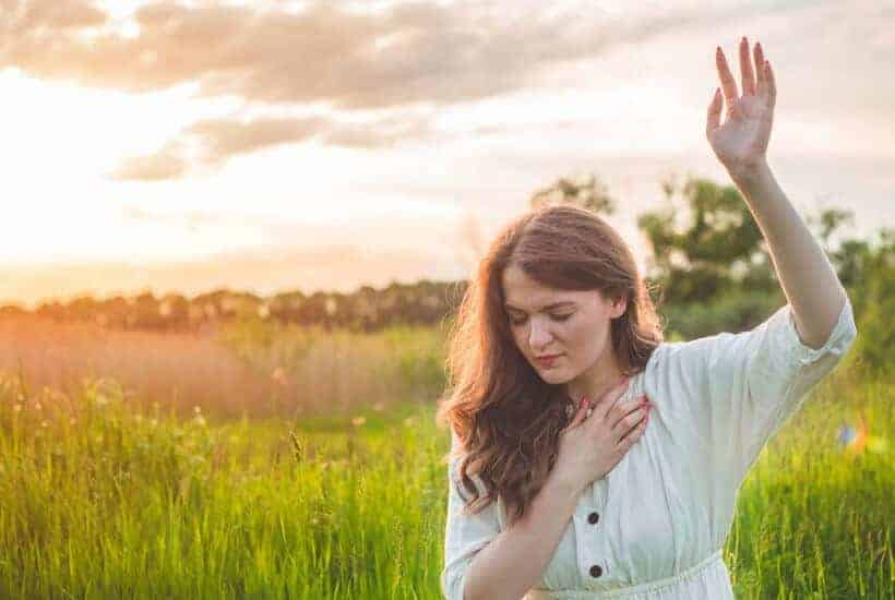 a woman on her knees in a field hand raised high praying How the Power of Prayer Changes Things