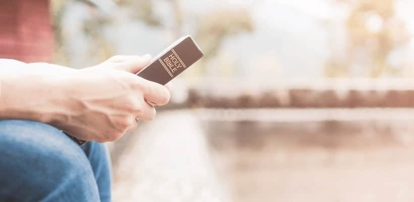 an image of a man sitting on a park park bench holding his bible featured image for Christian Testimony: The Importance of Sharing our Story