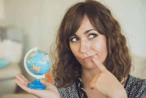 an image of a woman holding the world globe featured image for Jesus Christ will Reign Forevermore: Will You Be Ready?