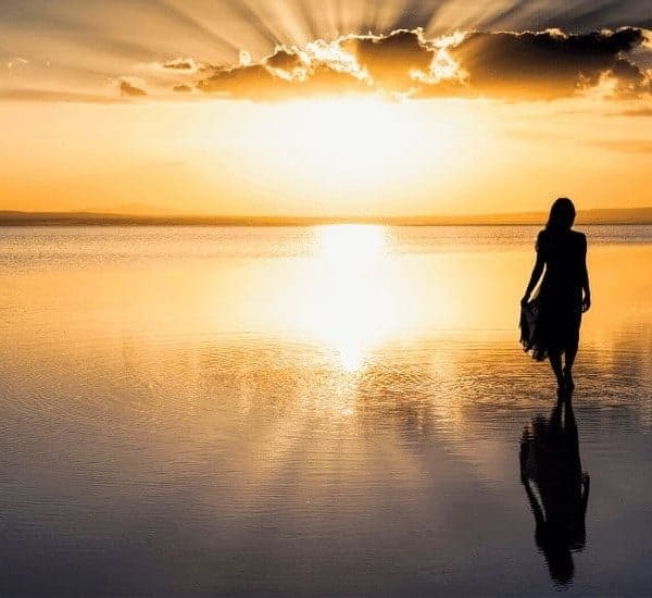 an image of a woman walking the beach with a golden sunset in the background. featured image for the importance of walking with God