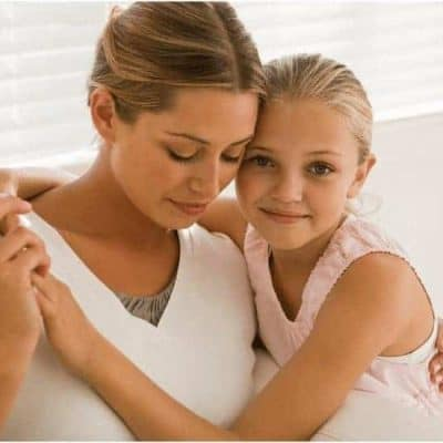 an image of a mother and small child sitting on a couch with their arms around one another with featured image for When Mother's Day is Hard