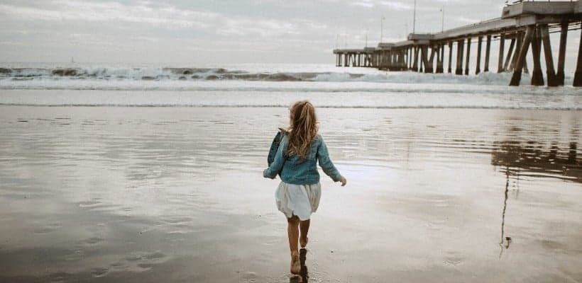 an image of a woman walking on the beach as the ocean waves are stormy with text reading Who is Your Refuge in the Storm? 3 Important Questions to Consider