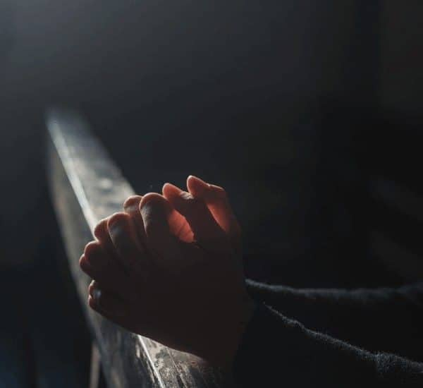 an image of a woman sitting on a church pew praying featured image for Do This in Remembrance of Me