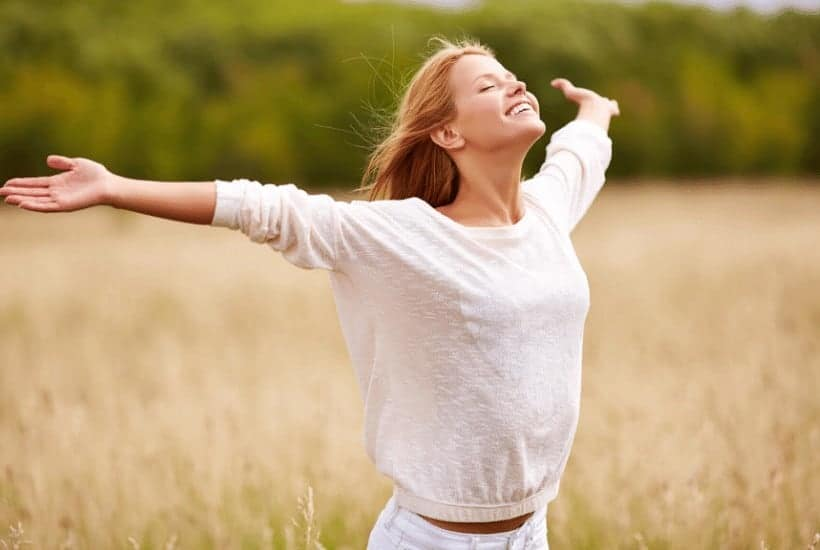 an image of a woman with her hands spread wide in an open field with text reading Worship God: A Pure Heart of Worship