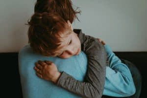 an image of a little boy being held and comforted featured image for 7 Ways of Coping With Loss and Grief