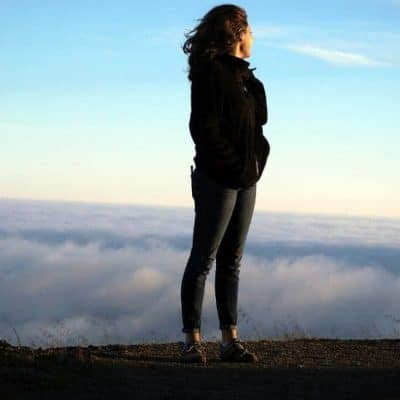 an image of woman overlooking a sunset over the horizon overcoming the spirit of fear concept