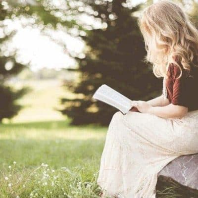 an image of woman reading the bible sitting on a rock featured image for The Gift of Salvation: 70+ Plus Bible Verses about Salvation