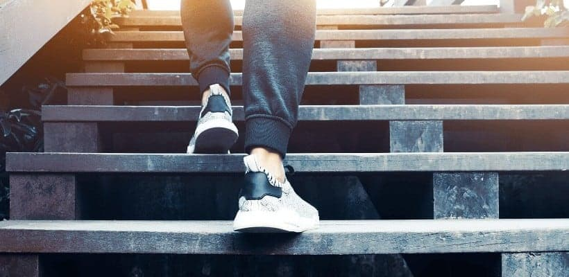 an image of a woman walking up a flight of steps. featured image for 5 Steps for Setting Spiritual Goals That Work in 2020