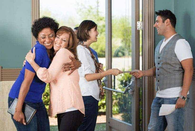 multicultural group of men and women hugging and greeting one another in a church auditorium Christian Living Featured