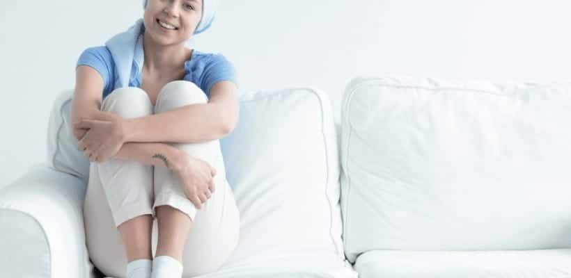 an image of a woman sitting on a couch who has cancer with text reading 8 Ways to Support Someone with Cancer