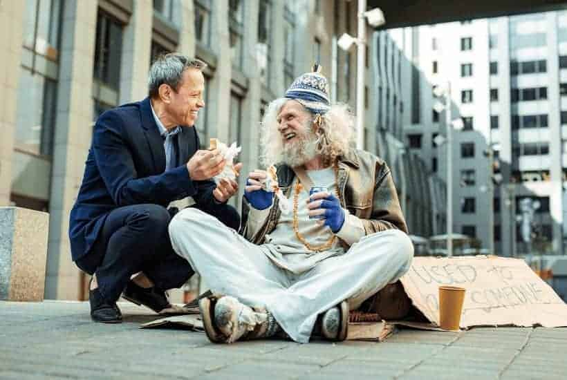 an image of a man approaching a homeless person person with something to eat. featured image for How to Show Acts of Kindness in the Midst of Chaos