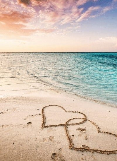 an image of a beach scene to two hearts carved in the sand featured image for 9 Ways to Guard Your Heart Biblically