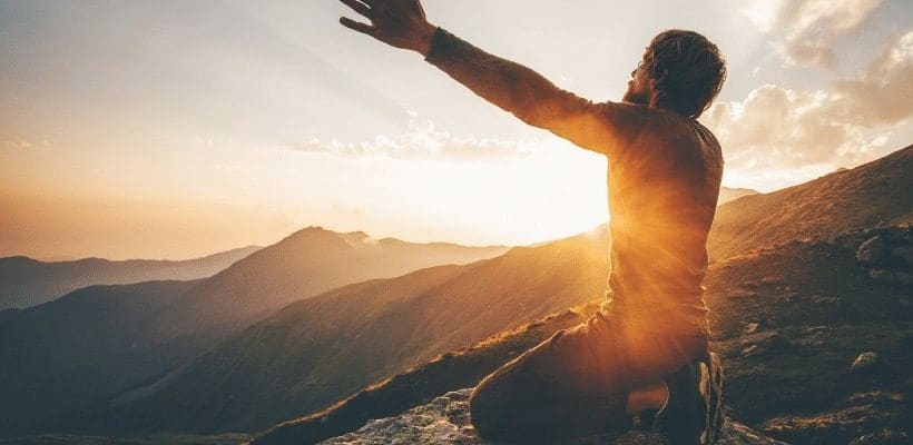 an image of a man on his knees with arms raised high with sunset in the background featured image for How God Answers Prayers in Unexpected Ways