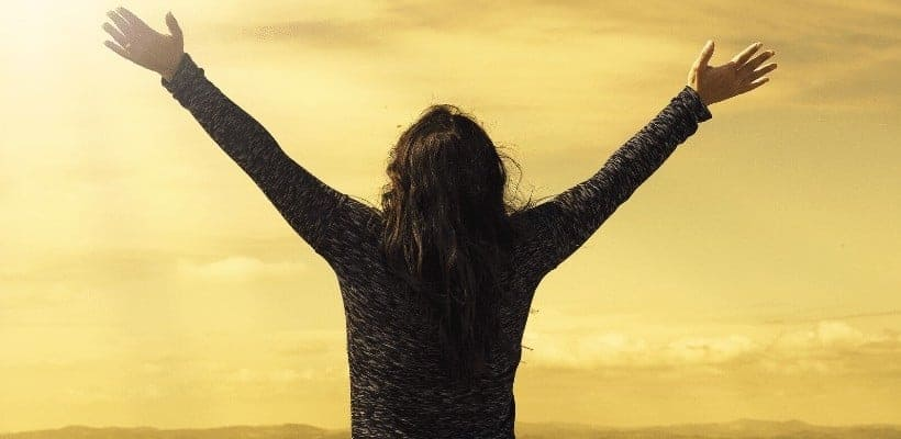 an image of a woman with both arms stretched towards the sky overlooking a golden sunset over a mountain featured image for What Does the Bible Say About Peace?