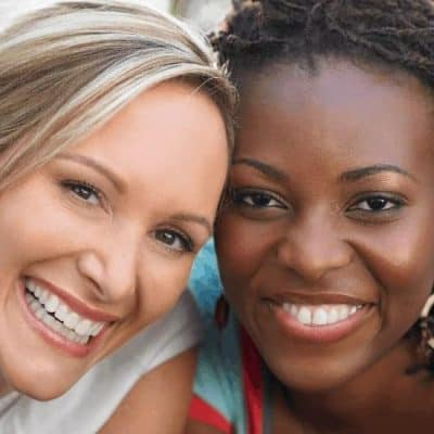 an image of a black and white woman friends smiling featured image for Unity in Diversity 7 Ways to Diffuse Your Anger