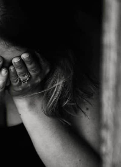 an image of a woman with her hands over her face with her head down featured image for What Does the Bible Say About Fear?