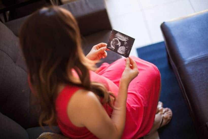 an image of a pregnant women holding an ultrasound photo of her baby featured image for What Does the Bible Say About Abortion?