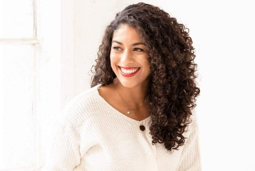 an image of a woman wearing a white sweater smiling featured image for 35 Prayer Prompts to Reboot Your Prayer Life