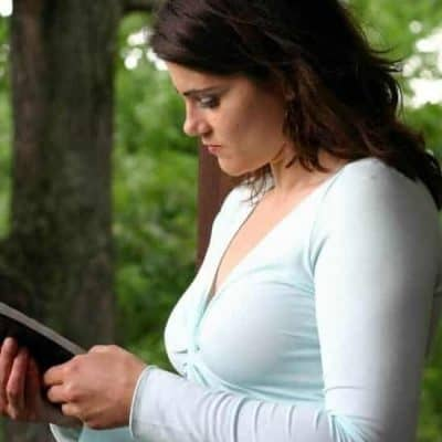 an image of a woman wearing a white dress reading her bible featured image for Religion vs Relationship with Jesus Christ: Do You Know the Difference?