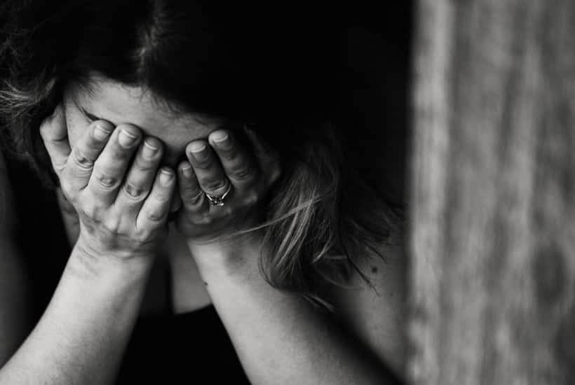 an image of a woman clasping her hands to her face crying featured image for Shattered: Mad at God