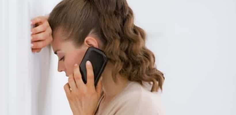 an image of a woman wearing a beige sweater leaning against a door holding a cell phone Tips to Overcome Fear Biblically in 10 Action Steps featured image