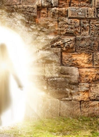 an image of Jesus walking from a stone tomb through a bright golden light featured image for The Resurrection of Jesus: What Does This Actually Mean for You?