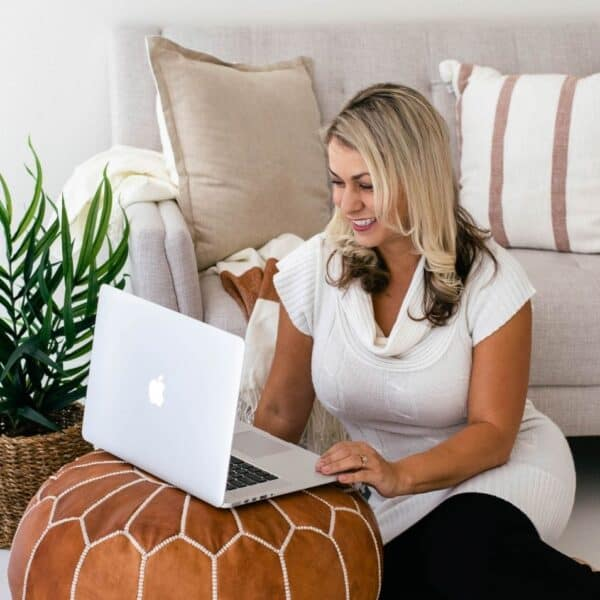 a woman sitting on a white couch drinking from a cup with a white opened laptop in front of her featured image for Resources for Christian Women
