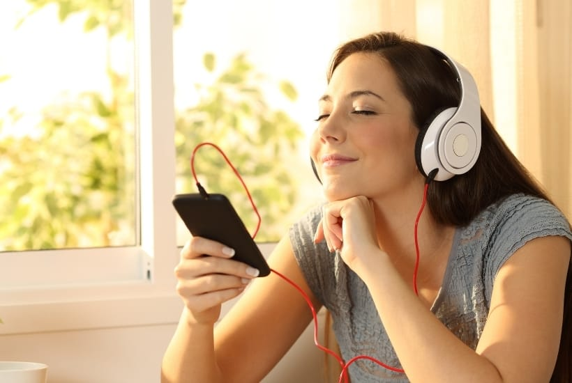 a brown haired woman wearing a gray t-shirt with white headphones on listening to music featured image for The Perfect Christian Playlist For Summer 2021