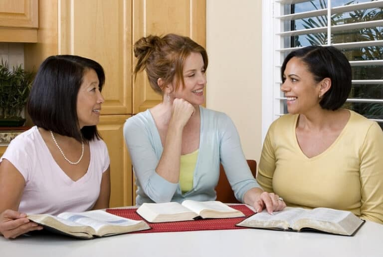3 women sitting at a kitchen table with bible open in a deep conversation featured image for What is the Good News of the Gospel? 35 Best Verses